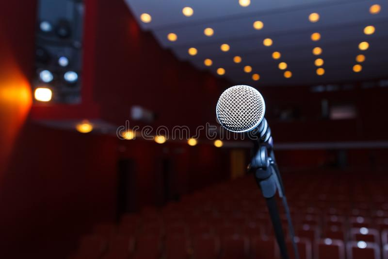 Micrófono en un fondo del pasillo oscuro con el asiento para los espectadores foto de archivo