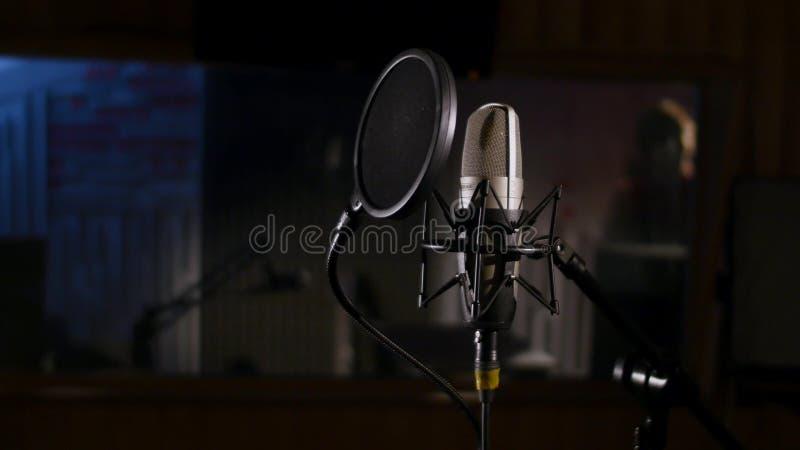 Micrófono en un soporte situado en una cabina de la grabación en estudio de la música bajo luz oscura imagen de archivo