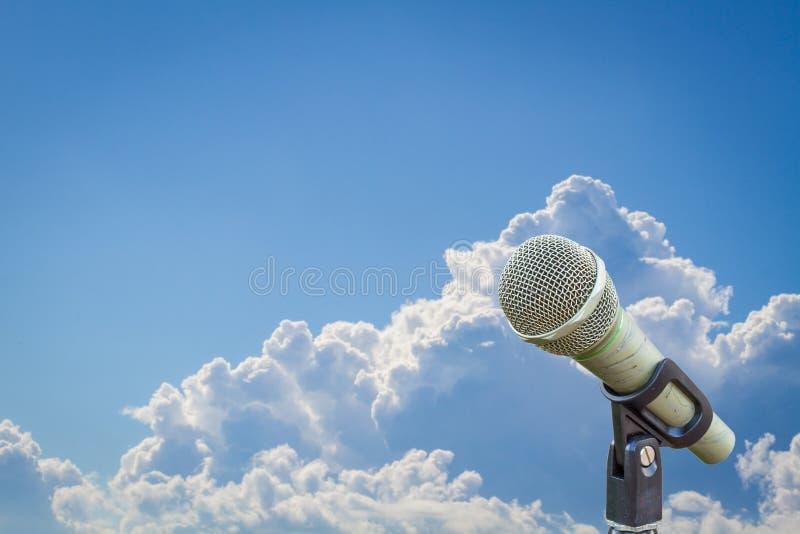 Micrófono en un soporte sobre el cielo azul nublado borroso imágenes de archivo libres de regalías