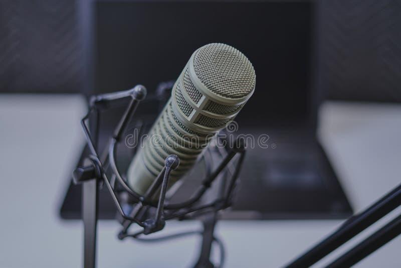Micrófono hecho un podcast con el ordenador portátil en fondo foto de archivo