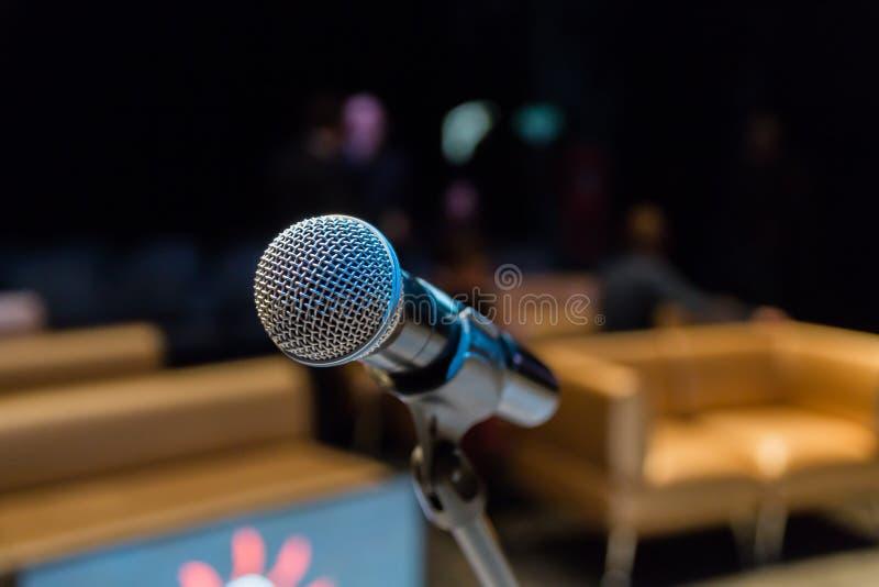 Micrófono inalámbrico en el soporte Fondo enmascarado Gente en la audiencia Demostración en etapa en el teatro o la sala de conci imagen de archivo libre de regalías