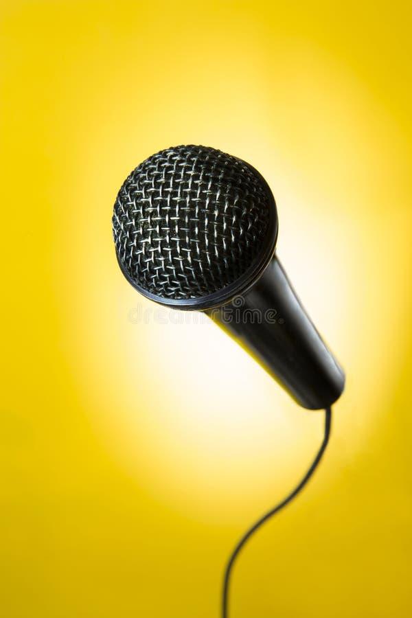 Micrófono negro en fondo amarillo foto de archivo libre de regalías