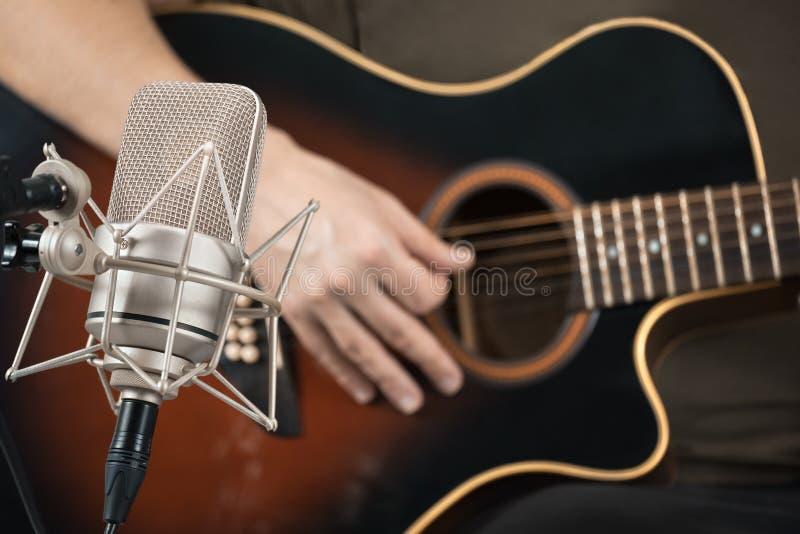 Micrófono que registra una guitarra acústica tocada a mano imagen de archivo