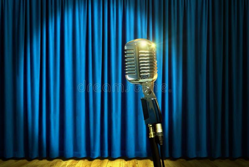 Micrófono retro en etapa sobre las cortinas azules fotografía de archivo