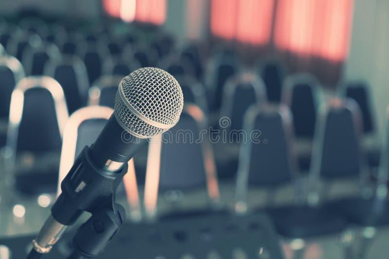 Micrófono sobre las sillas borrosas en la sala de conferencias imagenes de archivo