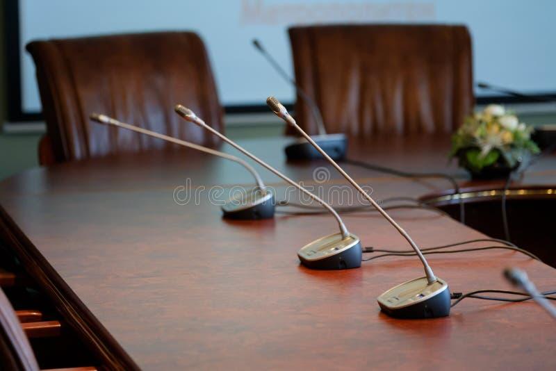 Micrófonos de la tabla en la sala de conferencias fotos de archivo libres de regalías
