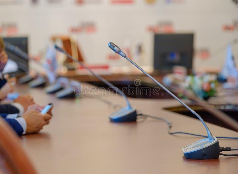 Micrófonos de la tabla en la sala de conferencias fotos de archivo