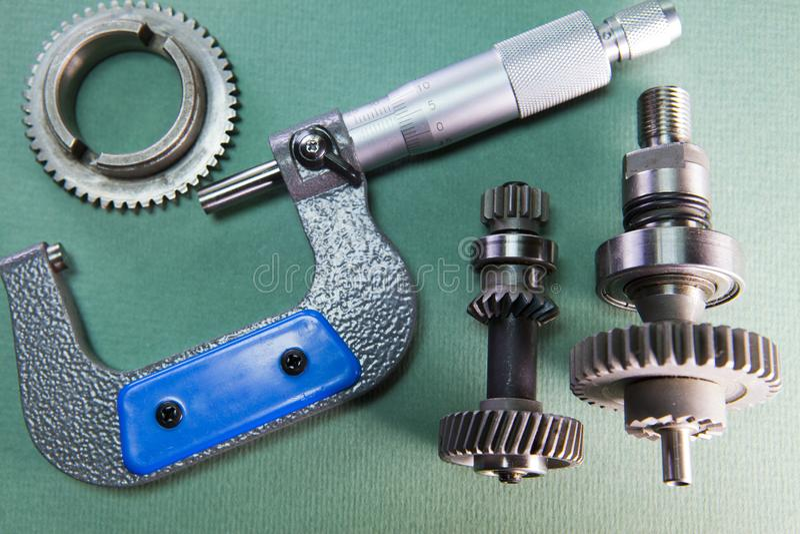Micrômetro e detalhe mecânicos em um fundo verde imagens de stock
