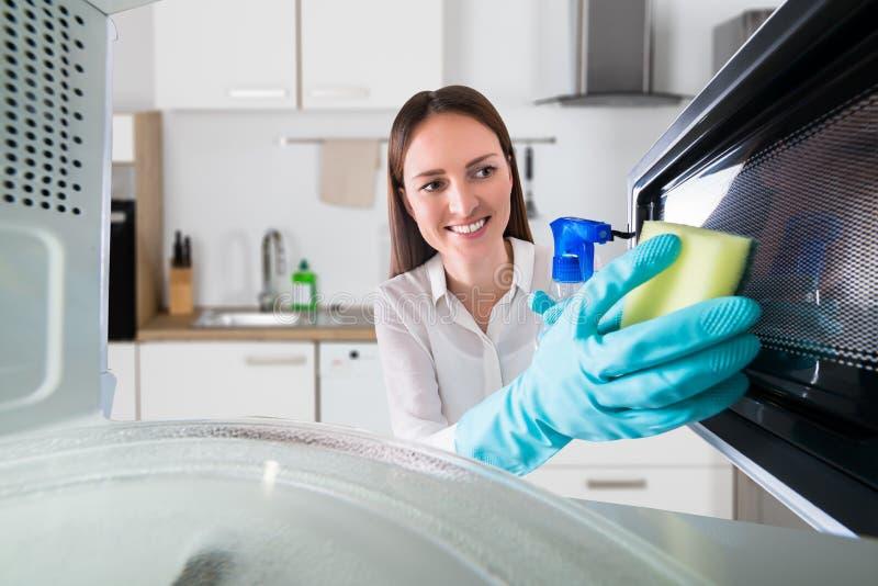 Micro-ondas da limpeza da mulher com garrafa e esponja do pulverizador imagem de stock