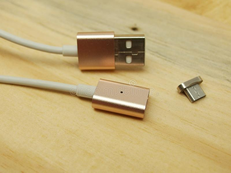 Micro usb adaptor with magnet conversion. Metal rose gold usb data cable charger with magnetic adaptor on wood planks background royalty free stock photography