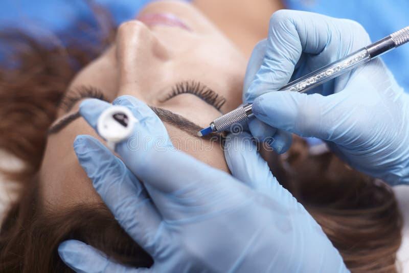 Microblading特写镜头,增加颜料到眼眉,妇女顶头面孔的手 免版税图库摄影