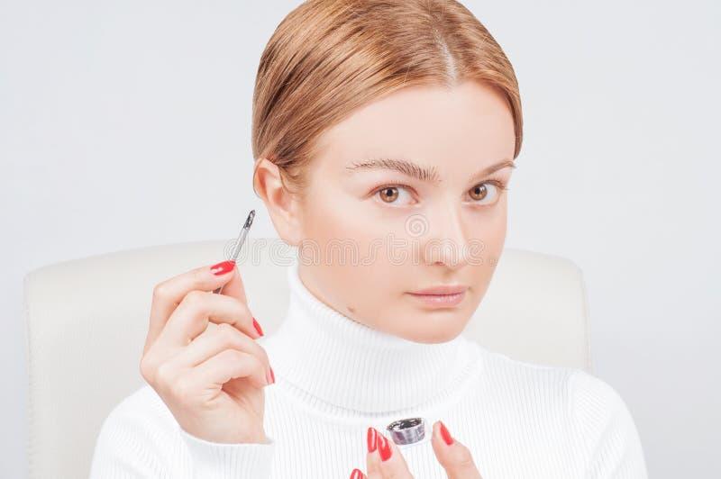 Microblading眼眉,妇女应用在眼眉的油漆无刺指甲花 专业眼眉关心,洗染和永久构成 免版税库存照片
