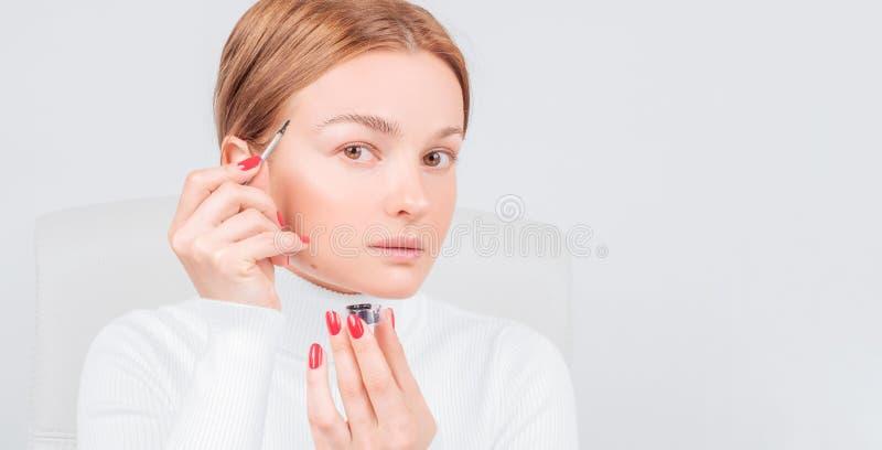 Microblading眼眉,妇女应用在眼眉的油漆无刺指甲花 专业眼眉关心,洗染和永久构成 免版税库存图片