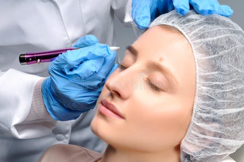 Microblading 做永久性的美容师构成 得到面部关心和纹身花刺眼眉的可爱的妇女 免版税图库摄影