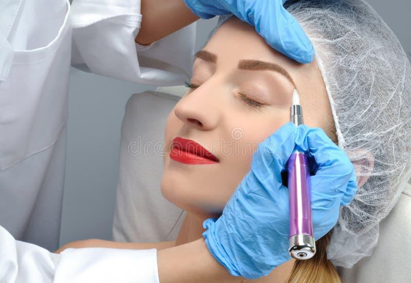 Microblading 做永久性的美容师构成 得到面部关心和纹身花刺眼眉的可爱的妇女 免版税库存照片