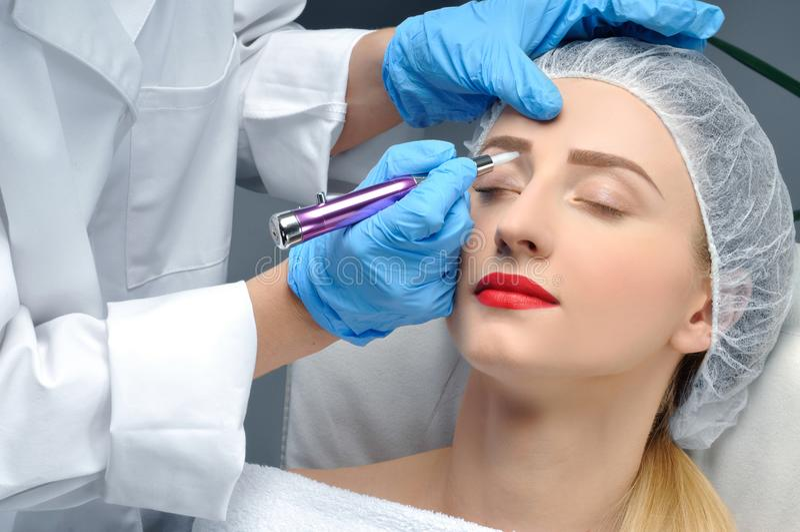 Microblading 做永久性的美容师构成 得到面部关心和纹身花刺眼眉的可爱的妇女 库存图片