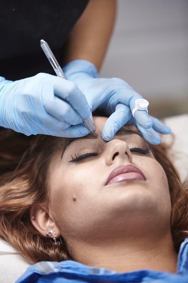 Microblading close up, eyebrow adding pigment into skin, close-up. Microblading close up, eyebrow adding pigment into skin, women head face royalty free stock image