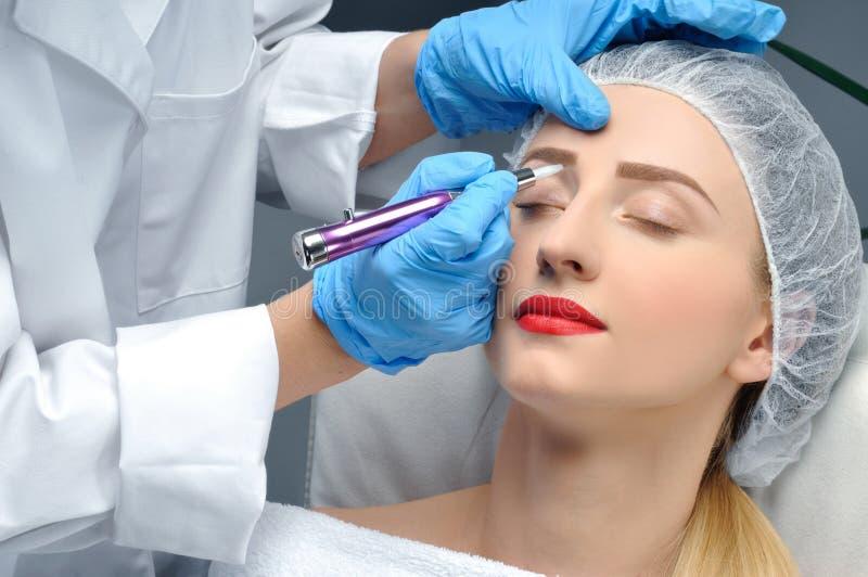 Microblading Cosmetologist que faz a composição permanente Mulher atrativa que obtém as sobrancelhas faciais do cuidado e da tatu imagens de stock