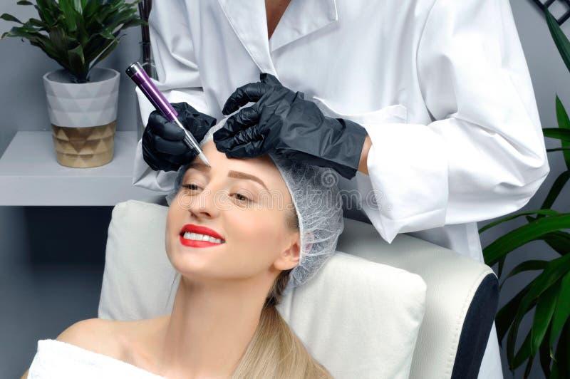 Microblading Cosmetologist que hace maquillaje permanente Mujer atractiva que consigue las cejas faciales del cuidado y del tatua imagen de archivo