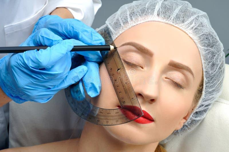 Microblading Maquillaje permanente Mujer atractiva que consigue cuidado y el tatuaje faciales imágenes de archivo libres de regalías
