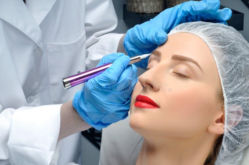 Microblading Maquillaje permanente Mujer atractiva que consigue las cejas faciales del cuidado y del tatuaje fotografía de archivo libre de regalías