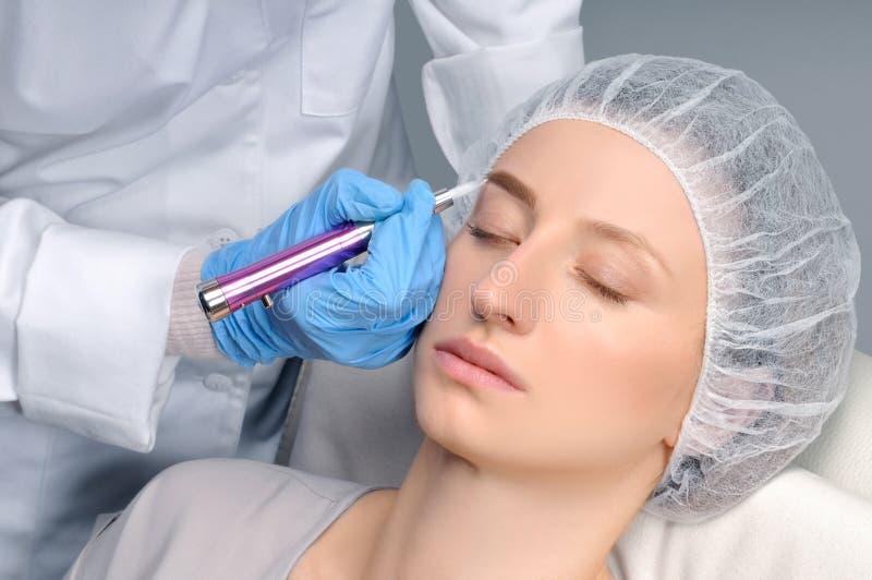 Microblading robi stałemu elementowi cosmetologist makeup Atrakcyjna kobieta dostaje twarzowe opieki i tatuażu brwi fotografia royalty free