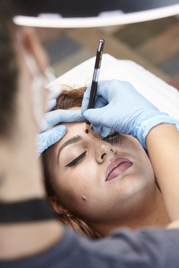 Microblading, woman drawing with pencil eyebrow shape. elevated view, stock images