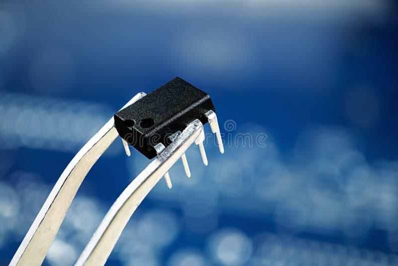 Microchip en las pinzas, cierre encima de la foto foto de archivo