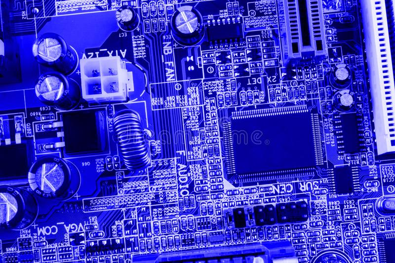 Microchip, filter, capacitors, battery, connectors on the motherboard of a modern computer blue background close macro royalty free stock photos