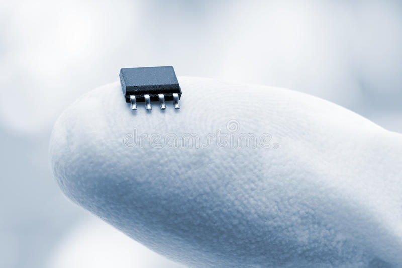 Microchip on a fingertip. Close up of microchip on fingertip against blue background stock photo
