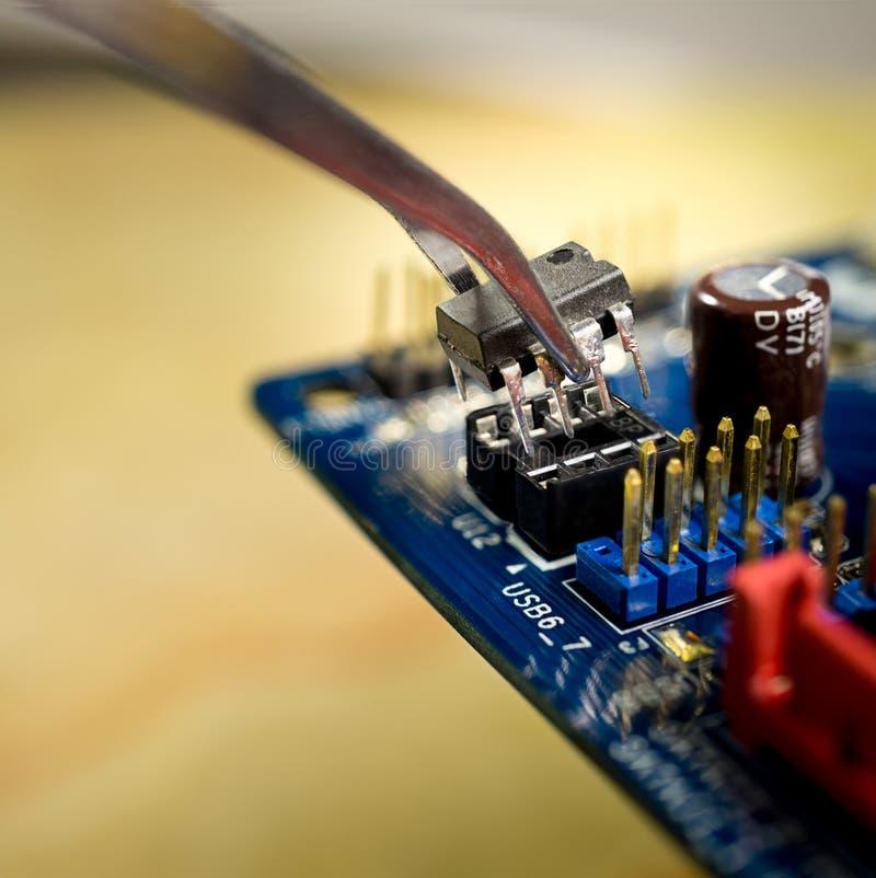 Microchip no cartão-matriz e no tweezer, fim acima da foto fotografia de stock