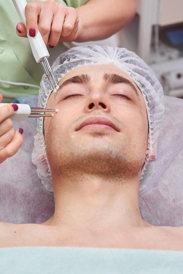 Microcurrent face therapy, young man. royalty free stock images