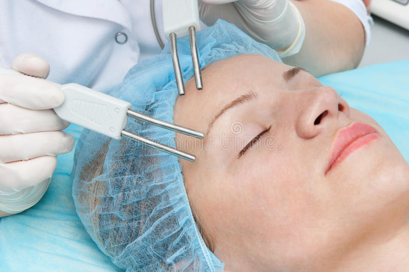 Microcurrent therapy. Young woman having microcurrent therapy by cosmetologist in beauty salon stock image