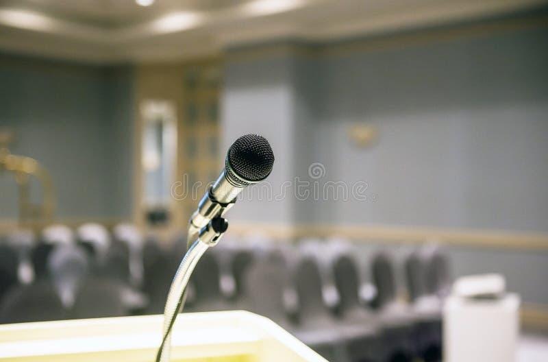 Microfone borrado sobre no fundo da sala ou da sala de conferências de seminário fotografia de stock royalty free