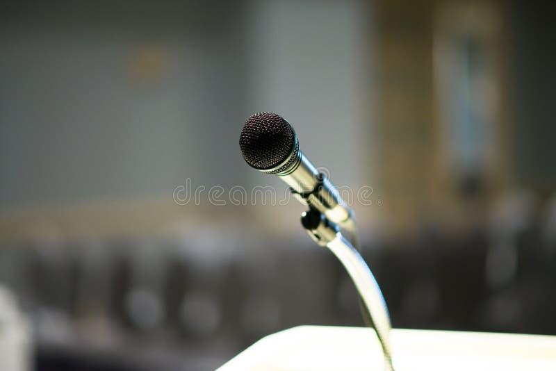 Microfone borrado sobre no fundo da sala ou da sala de conferências de seminário fotografia de stock