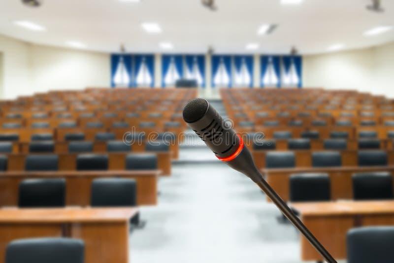 Microfone com a foto borrada da sala de conferências ou de sêmens vazios imagens de stock