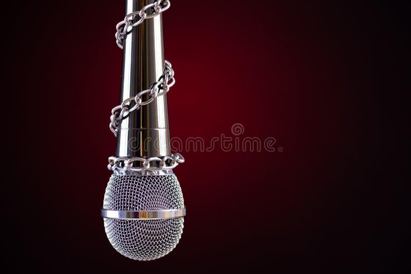 Microfone com uma corrente, descrevendo a ideia da liberdade de imprensa ou a liberdade de express?o no fundo escuro Imprensa do  ilustração do vetor