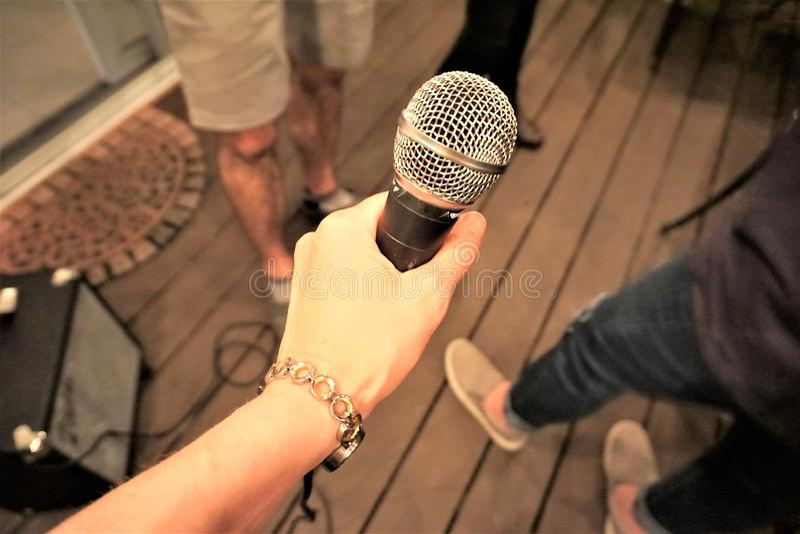 Microfone da terra arrendada da mão no partido fotografia de stock royalty free