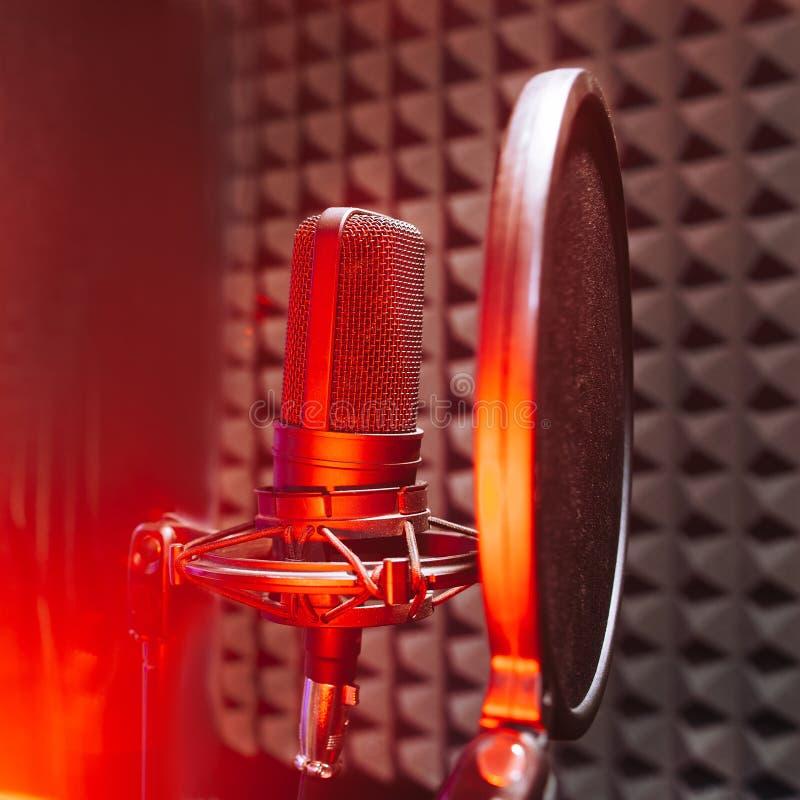 Microfone do estúdio com vermelho na luz do ar fotos de stock royalty free