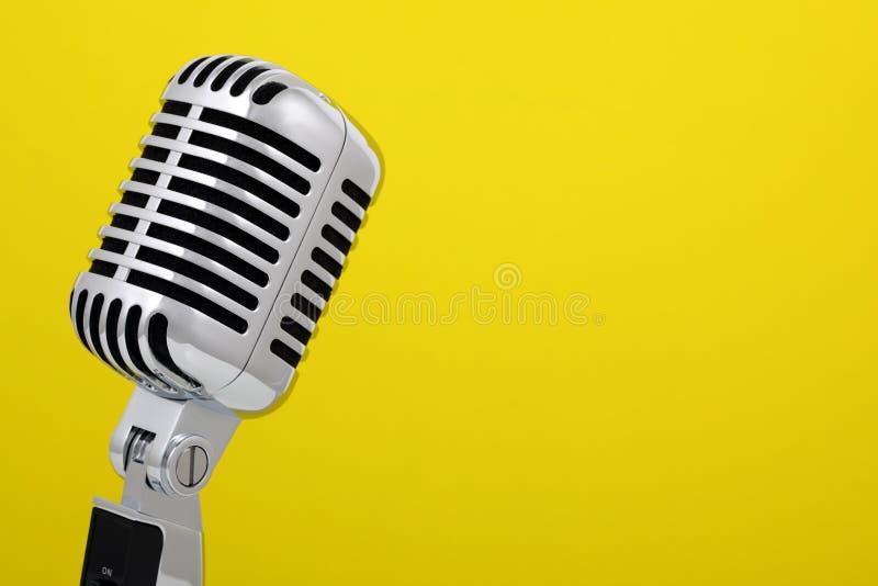 Microfone do vintage isolado no amarelo fotos de stock
