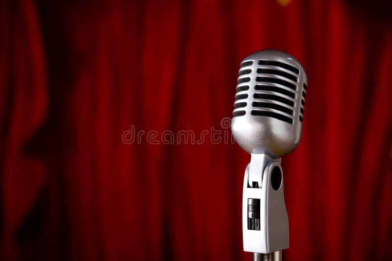 Microfone do vintage na frente da cortina vermelha imagem de stock