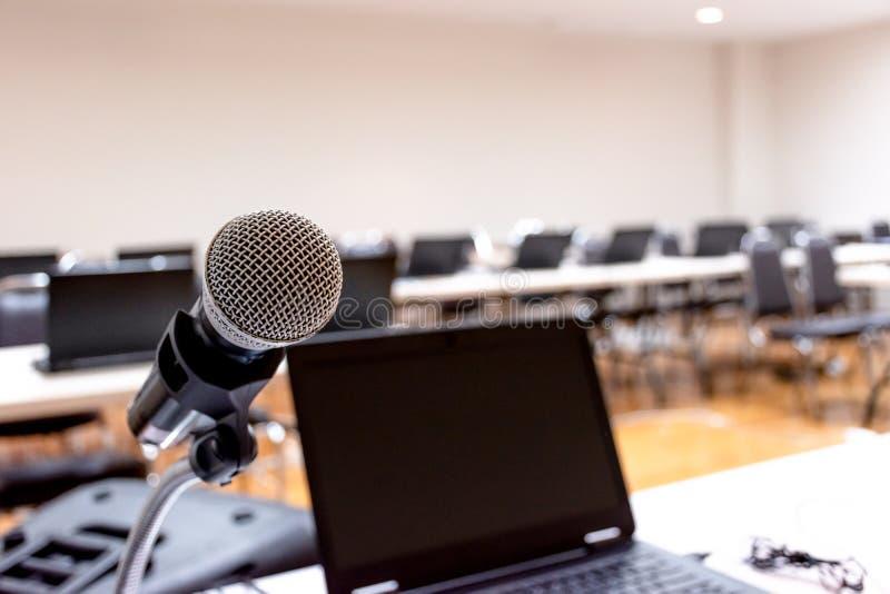 Microfone e caderno em abstrato borrados do discurso na sala de seminário imagens de stock royalty free