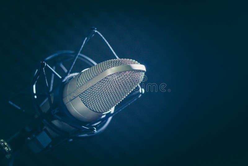 Microfone e console audio no fundo escuro fotografia de stock