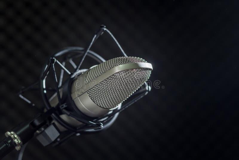Microfone e console audio no fundo escuro foto de stock