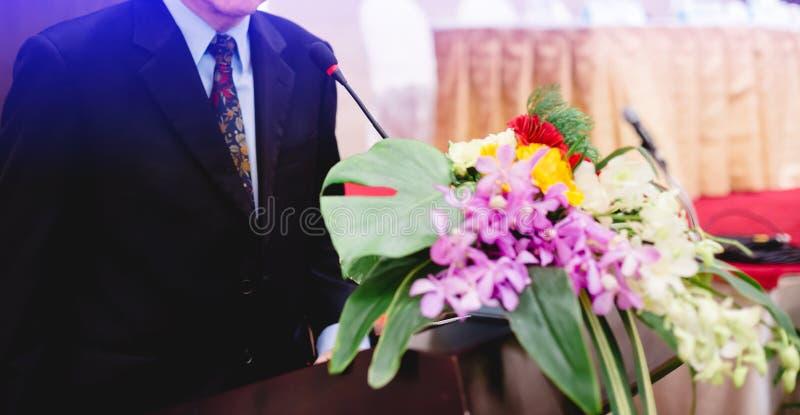Microfone e homem de negócio em um auditório para reunião dos acionistas ' foto de stock