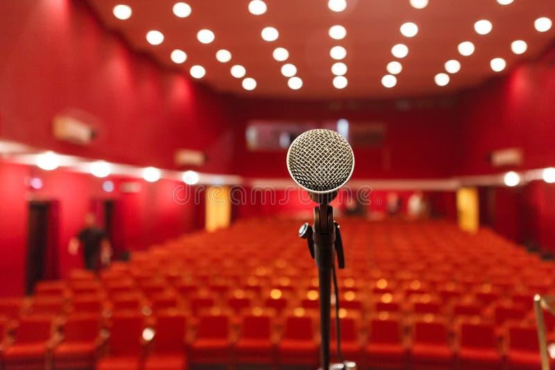 Microfone em um fundo do salão vermelho com assento para espectadores imagem de stock