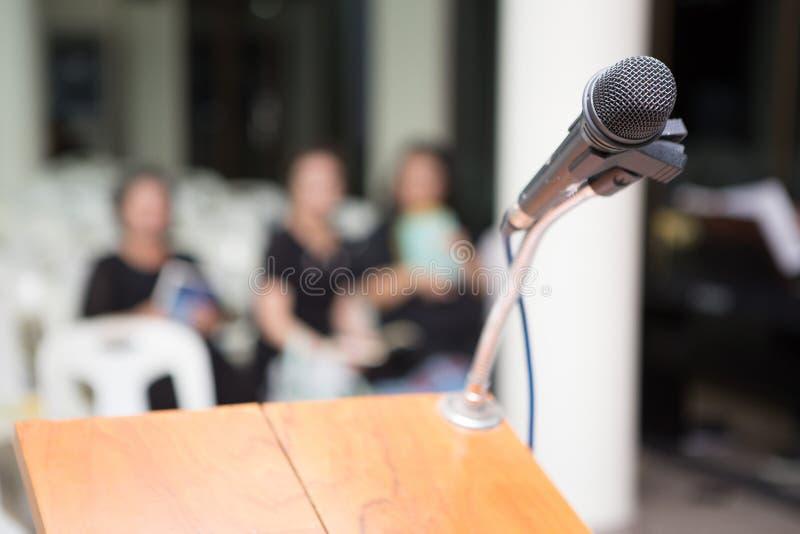 Microfone em vestir fúnebre do pódio e dos povos preto na igreja imagens de stock royalty free