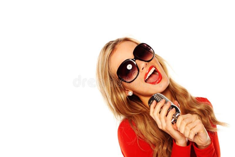 Microfone louro da terra arrendada do canto foto de stock