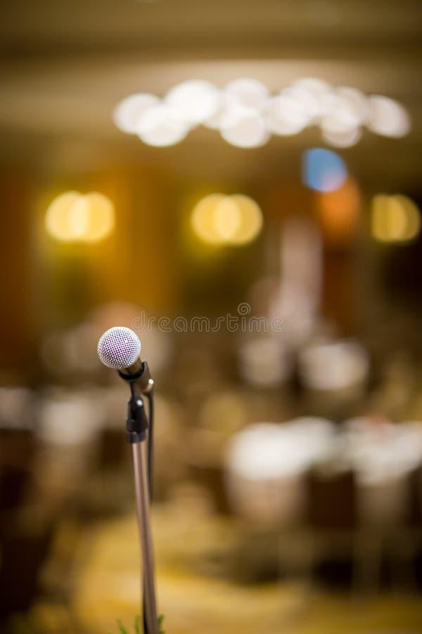 Microfone na sala de concertos ou na sala de conferências macia e no estilo do borrão para o fundo O microfone sobre o sumário bo imagens de stock royalty free