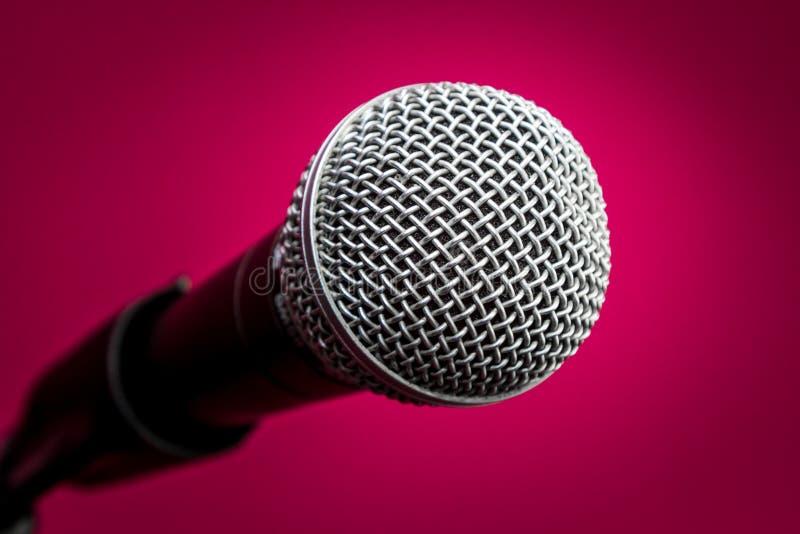 Microfone no fundo carmesim, close-up fotografia de stock